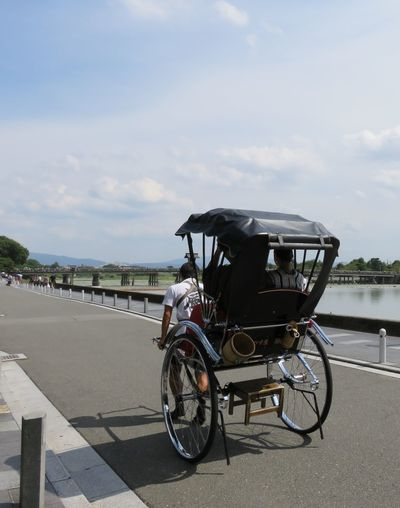 Rear view of man riding pedicab on road