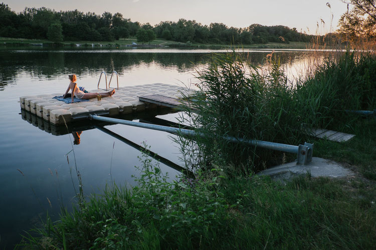 Woman resting on floating platform in lake during sunset