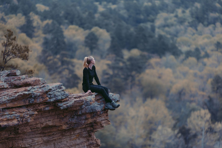 Side view of woman sitting on rock