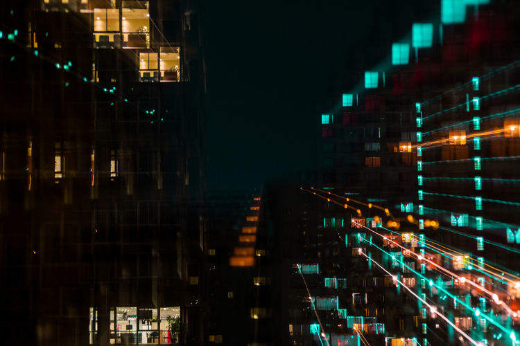 Blurred motion of illuminated buildings in city at night