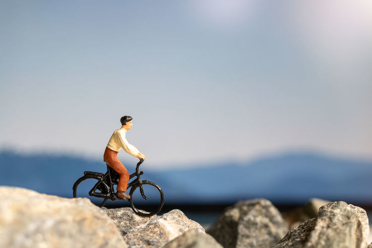Man with bicycle on rock against sky