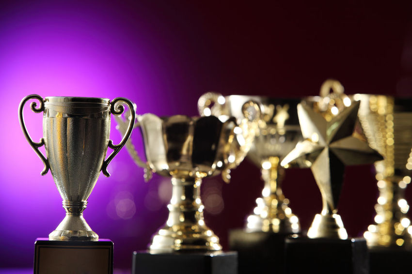 group of golden trophy on the purple background AWARD Achievement Celebration Champion Contest Effort First Place  Golden Shiny Trophy Ceremony Competition Cup Glow Group Of Objects Honor Leadership Light Spot Metal Metallic Prize Purple Success Victory Winner