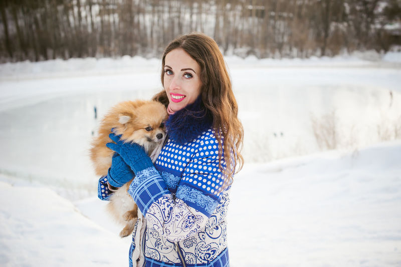 Portrait Of Woman With Puppy Standing On Snow