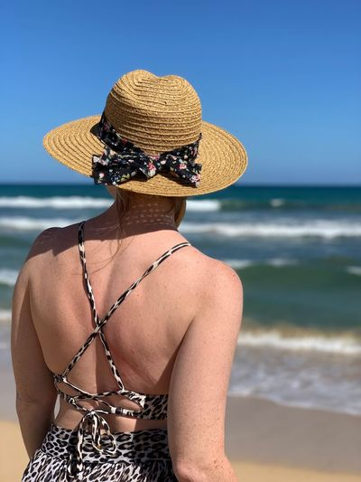 Rear View Of Woman Wearing Hat Against Sea At Beach