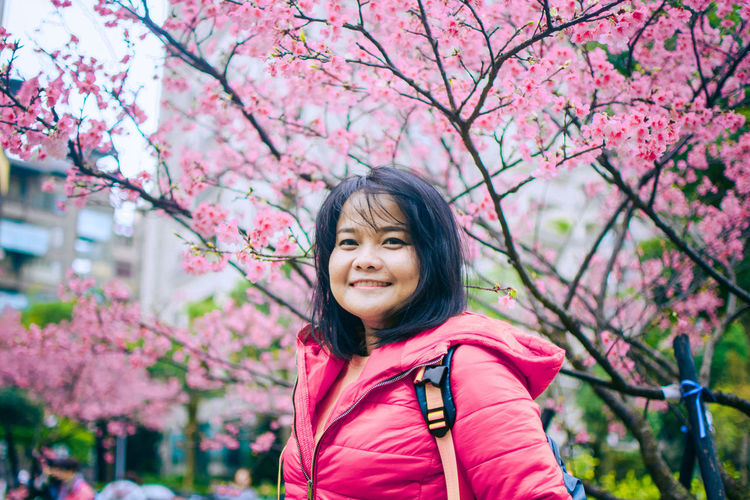 Portrait of smiling woman against pink cherry blossoms