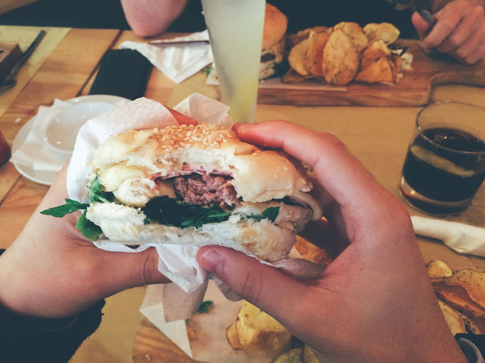 Cropped hands of person having burger at table