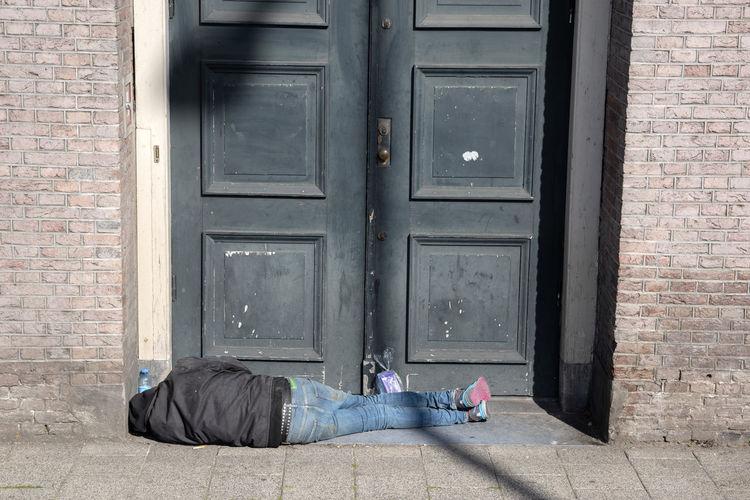 Man sleeping by closed door of building