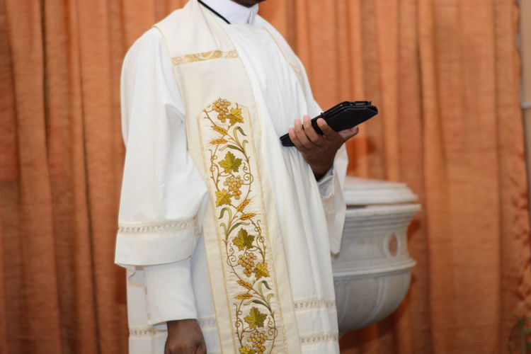 Midsection of priest holding bible while standing against curtain in church