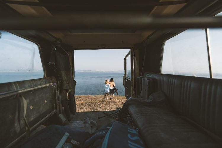 People in bus by sea against sky
