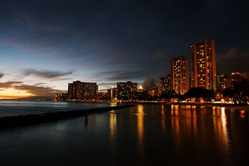 City lights in Hawaii Architecture Building Exterior Water Built Structure Sky Illuminated City Reflection Building Waterfront Urban Skyline Cityscape Night