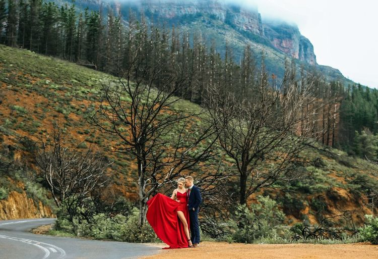 Full length of elegant couple standing on road by mountain