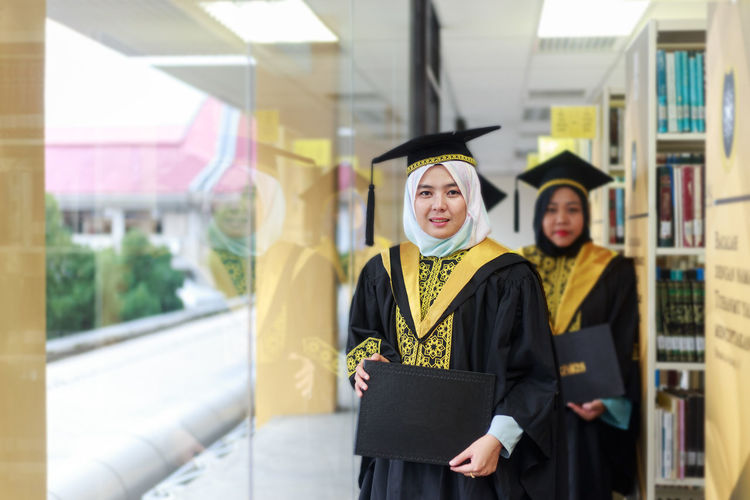 Portrait of woman smiling with graduation and convocation dress in library. Copy space. Achievement Architecture Built Structure Education Front View Graduation Graduation Gown Learning Mortarboard Outdoors People Portrait Real People School Standing Student University University Student Waist Up Women Young Adult