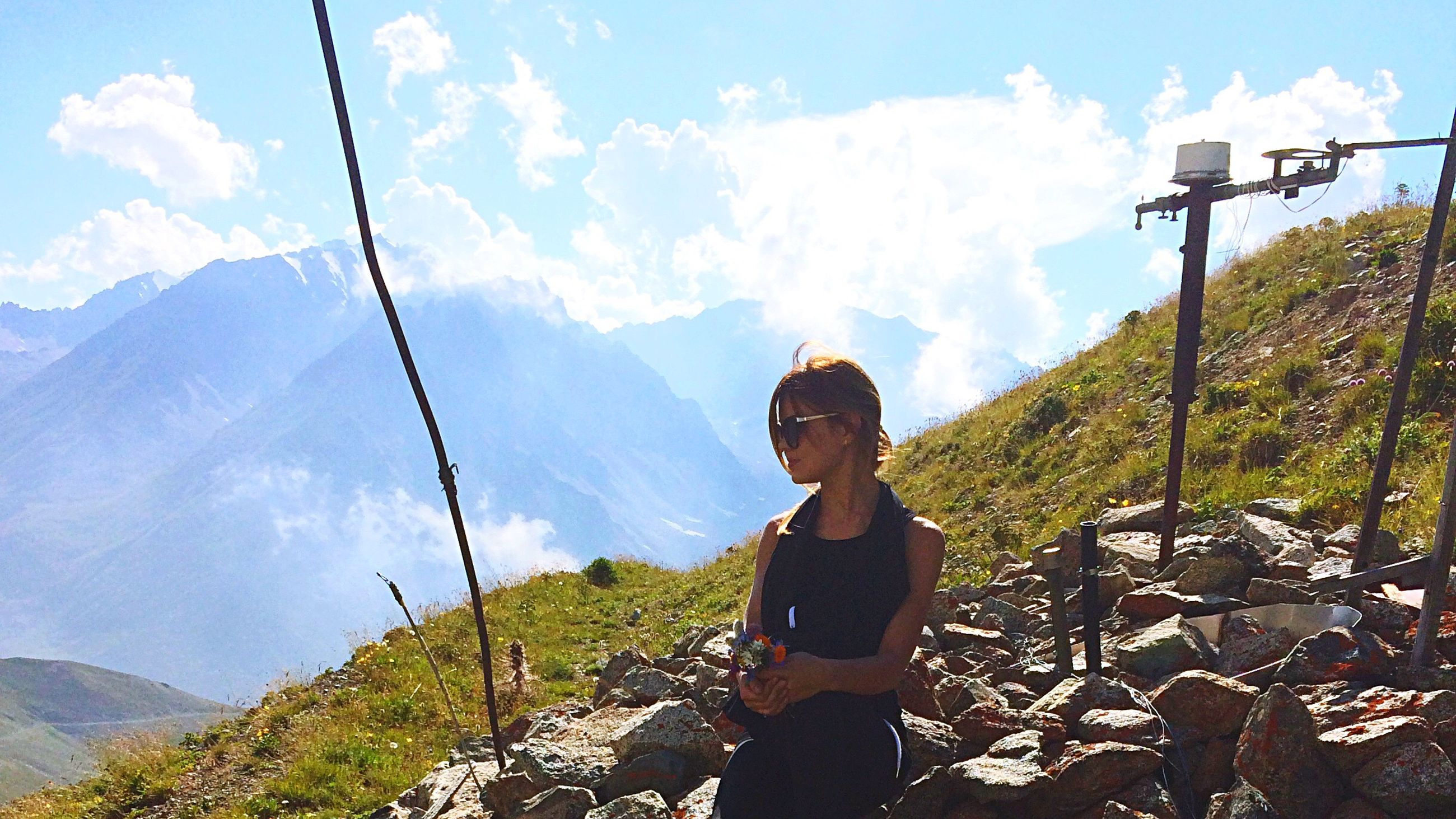 sky, sitting, mountain, casual clothing, cloud - sky, outdoors, day, young adult, in front of, scenics, mountain range