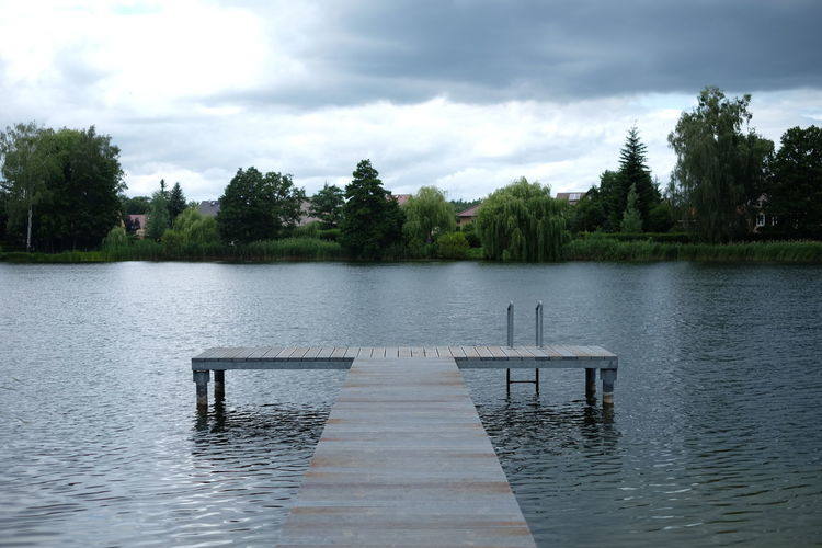 Empty Jetty At Lake Against Cloudy Sky