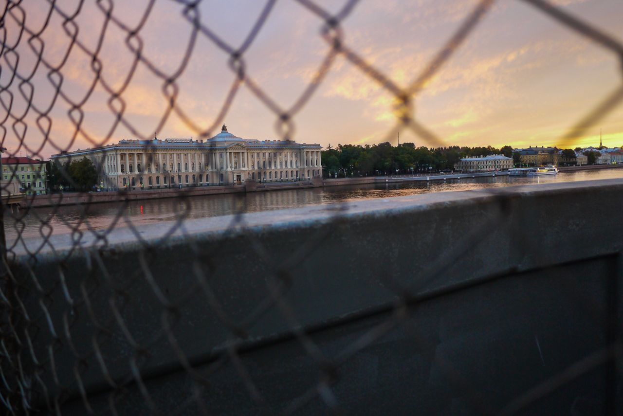 Close-Up Of Chainlink Fence Against River In City