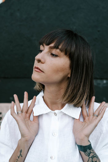 Close-up of woman standing against wall outdoors