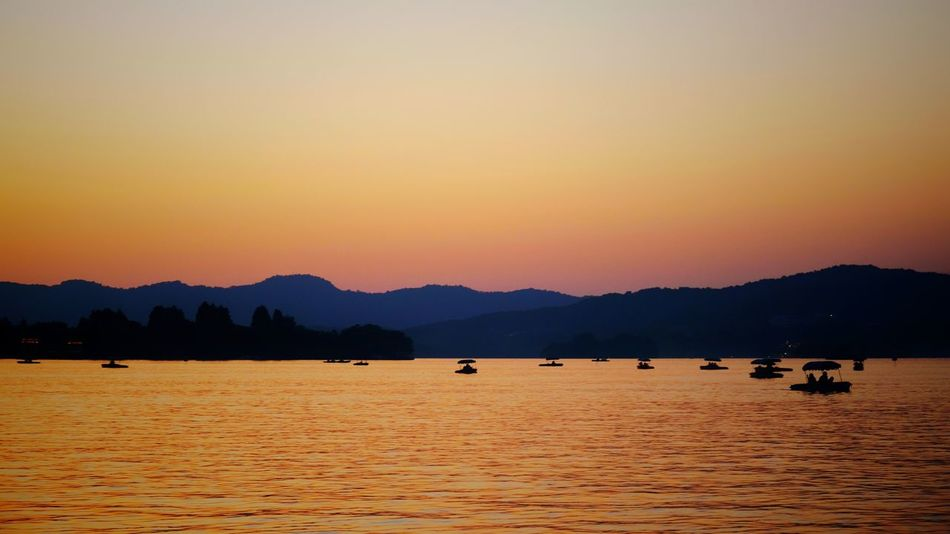 Mountain Landscape Lake Nature Outdoors Water Scenics Tranquility Lake View China View West Lake, Hangzhou Hangzhou,China Light And Shadow Travel Vacations Warm Glow Yellow Beauty In Nature Floating On Water Summer Sunset Silhouette Mountain Range Houseboat Cityscape