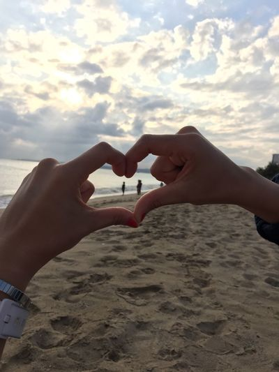 Cropped image of woman forming heart shape with hands at beach