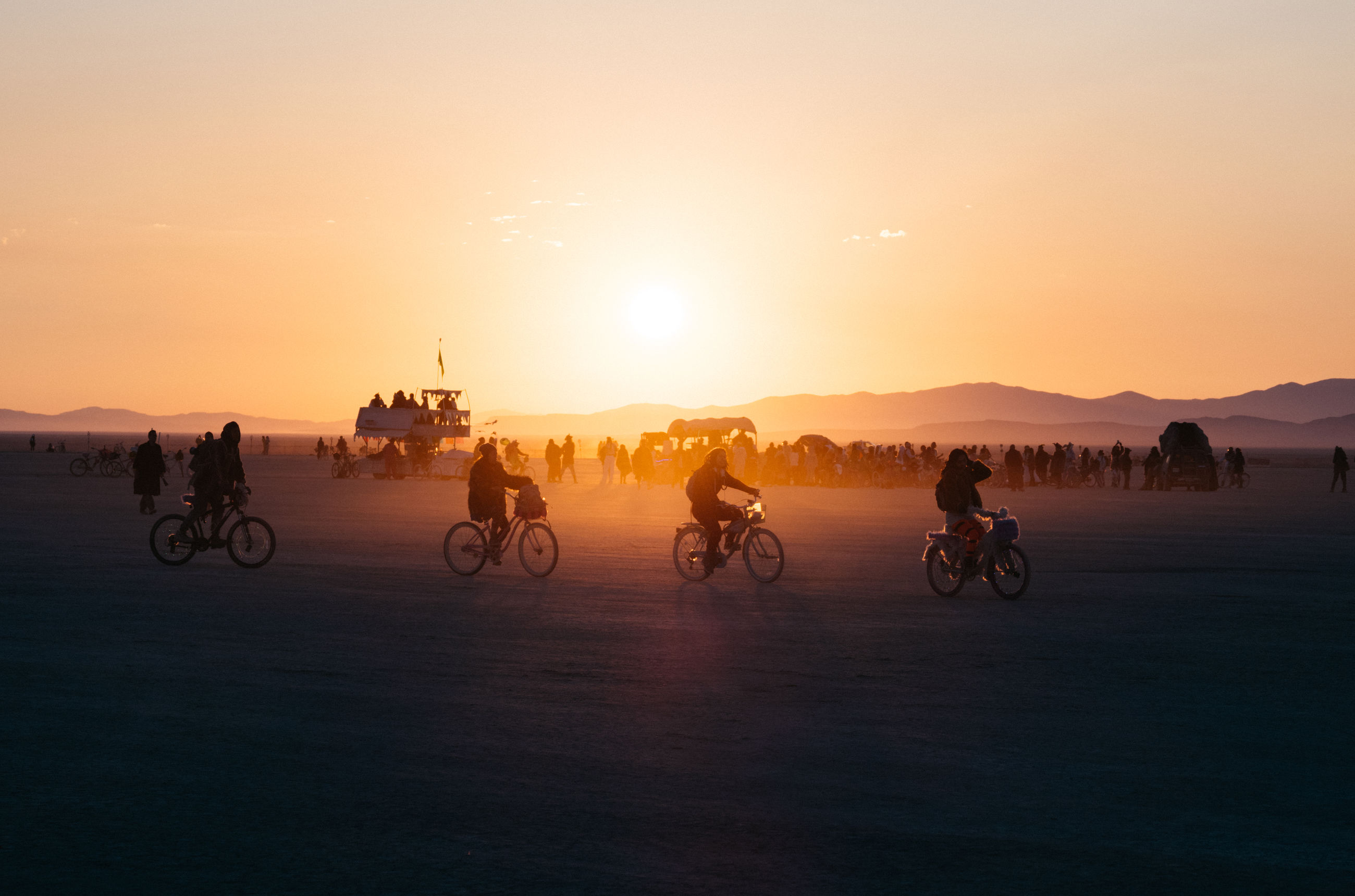 sunset, sky, transportation, beauty in nature, orange color, mode of transportation, real people, scenics - nature, group of people, sun, land vehicle, bicycle, sport, water, nature, riding, ride, lifestyles, travel, silhouette, outdoors