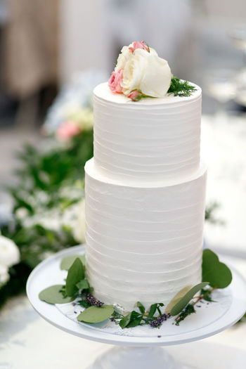 White wedding cake with flowers Food Freshness Focus On Foreground Healthy Eating Close-up White Color Ready-to-eat No People Dessert Indulgence Sweet Food Wellbeing Sweet Cream Green Color Table Serving Size Temptation Crockery Leaves Decoration