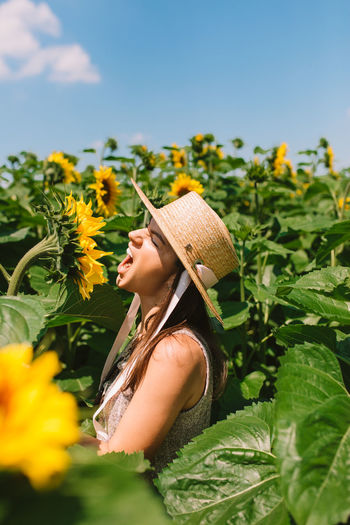 Woman with straw hat in sunflower field