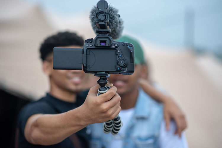 Selfie Holding Photography Themes Tripod Real People Obscured Face Communication Casual Clothing Close-up Portrait Adult Activity Standing Day Men Front View Camera - Photographic Equipment People Focus On Foreground Technology Selfie