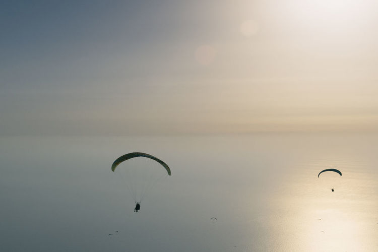 Low angle view of silhouette person flying over sea against sky