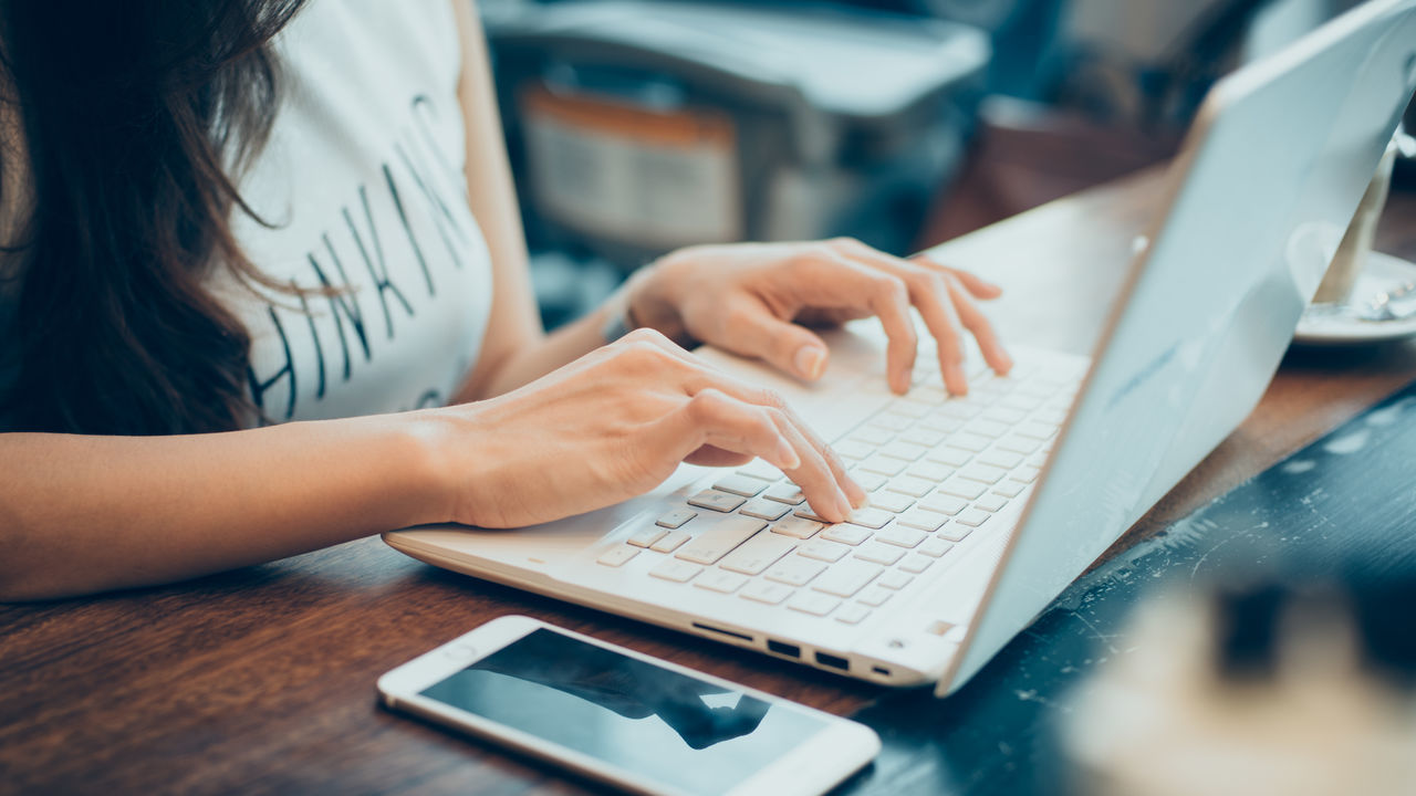 Midsection Of Woman Using Laptop At Cafe