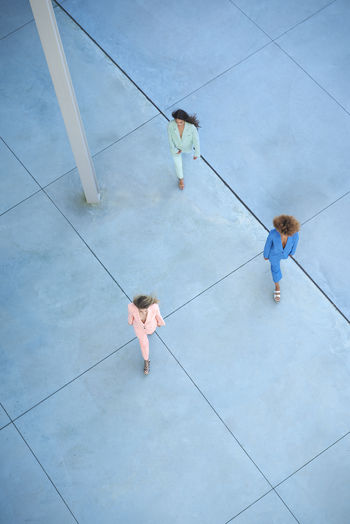 High angle view of people holding umbrella on floor