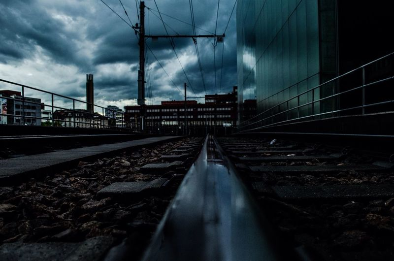 Railroad track against cloudy sky