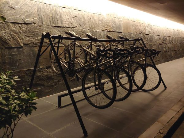 time for some night riding. A set of black road bikes lined up in a rack. Looks sinister. Sinister Evil Plans Suspicious Objects In A Row Repetition Thief Getaway Vehicle Under The Cover Of Darkness Bicycle Rack Bicycle Stationary Land Vehicle Cycling Racing Bicycle Parking Lot