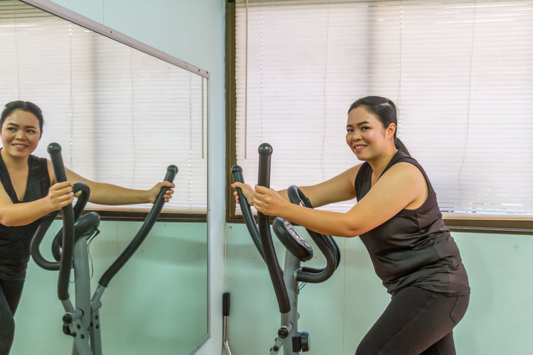 Smiling woman exercising by mirror at gym