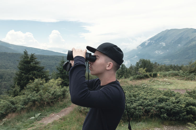Side View Of Teenage Boy Looking Through Binoculars On Land