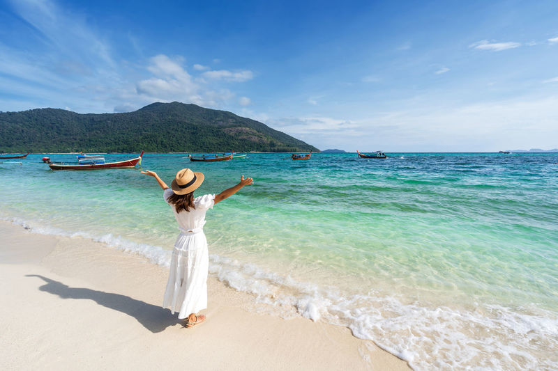 Woman enjoying at beach against sky