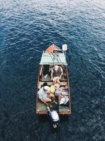 High Angle View Of Men Fishing On Boat In Sea
