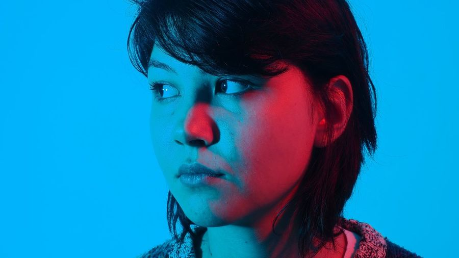 Close-up of woman looking away against blue background