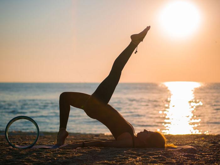 Woman doing yoga at beach against sky
