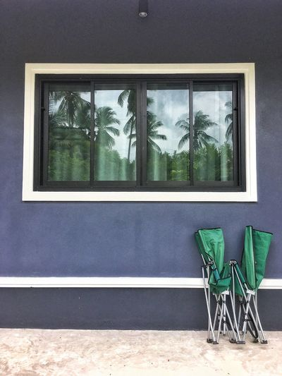 The folding bed is placed on the wall of the house, in a mirror with the shadow of a coconut tree.