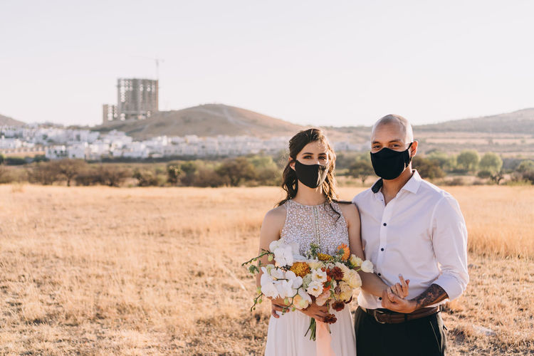 Young couple standing on field with masks on