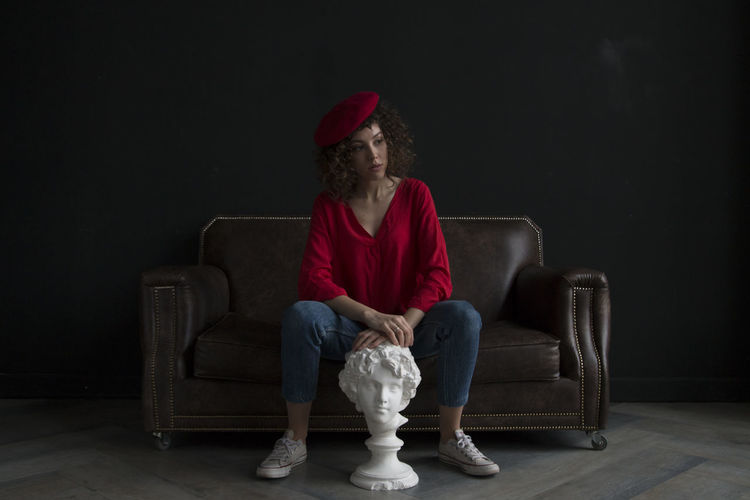 Portrait of woman sitting on sofa against wall