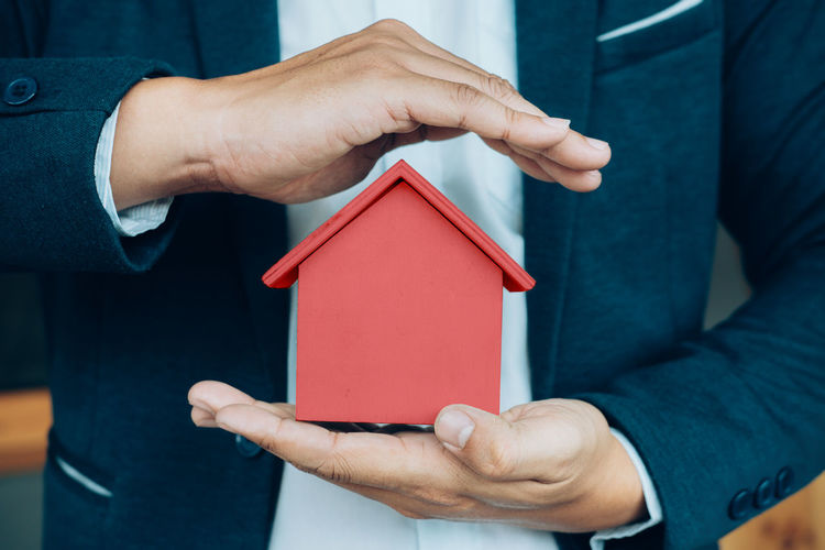 Close-Up Of Man Holding Red Model Home