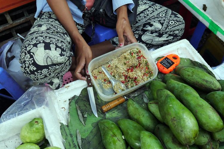 Low section of woman selling raw mangoes and guavas at street market