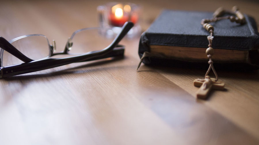 Close-up of eyeglasses and bible on table