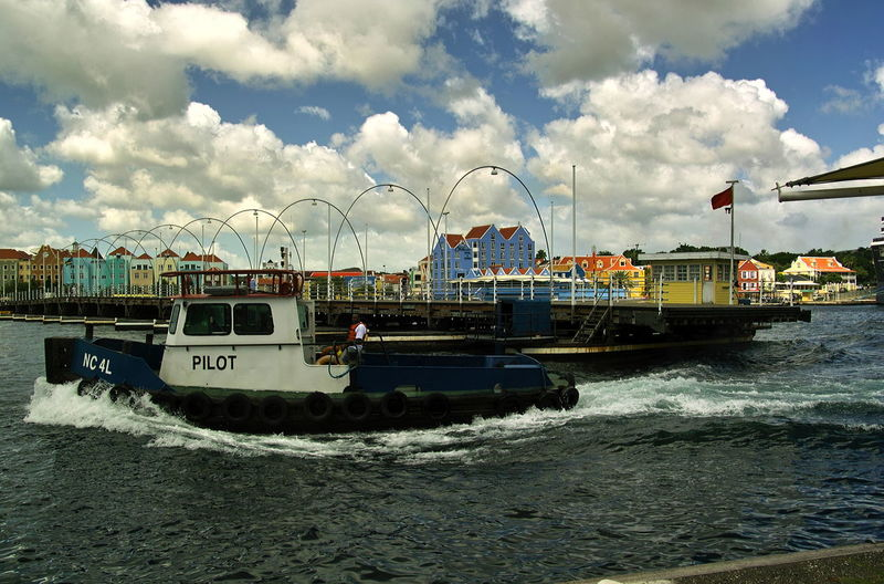 Pilot's boat speeding past the opened Queen Emma Bridge, a ponton bridge at Willemstad harbor Bridge - Man Made Structure City Cloud - Sky Day Ferry Lifestyles Mode Of Transport Motion Nautical Vessel No People Outdoors Pilot Pilot's Boat Punda Curacao Queen Emma Bridge Sea Sky Transportation Travel Destinations Water Waterfront Willemstadt Harbour
