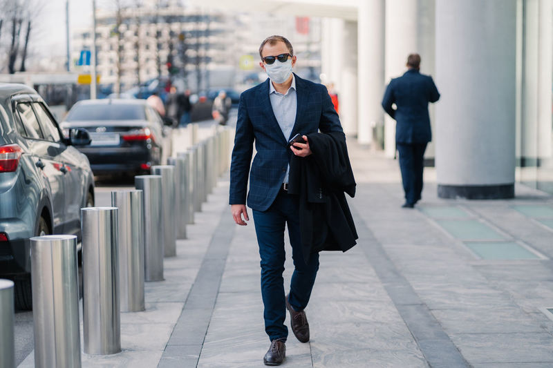 Businessman wearing mask walking in city