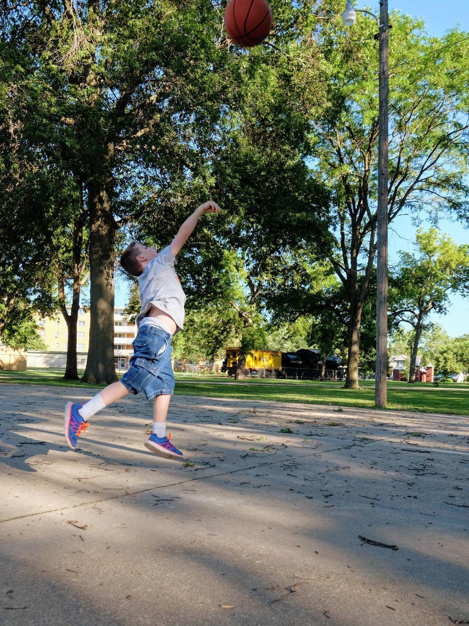Full Length Of Boy Playing Basketball At Park