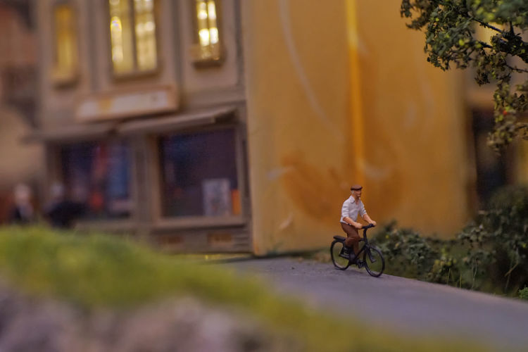 Man riding bicycle on street against buildings in city