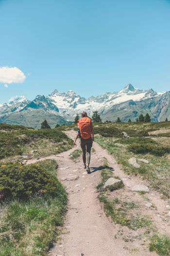 Adventure Backpack Beauty In Nature Day Full Length Grass Hiking Leisure Activity Lifestyles Men Mountain Mountain Range Nature One Person Outdoors People Real People Rear View Scenics Sky Standing Walking Summer Exploratorium