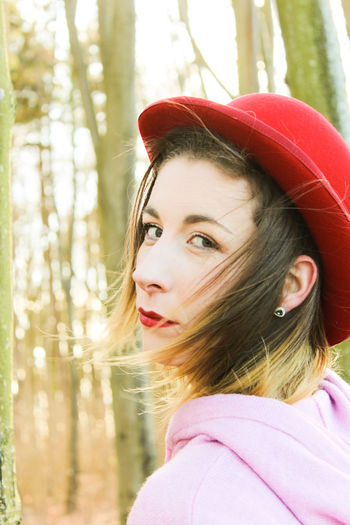 Close-Up Portrait Of Beautiful Woman Wearing Red Hat In Forest