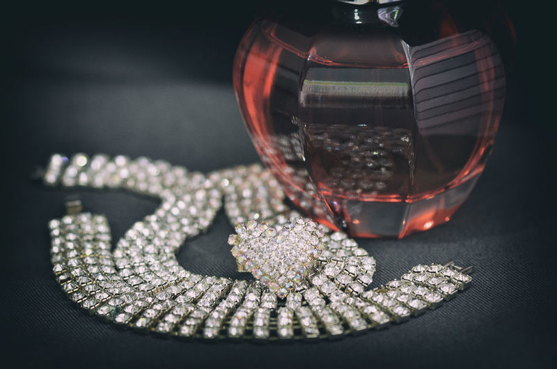 High angle view of necklace with perfume on table